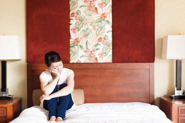 ベッドの上で寝違えに悩む女性