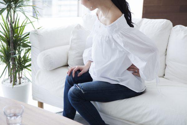 左腰を押さえる女性