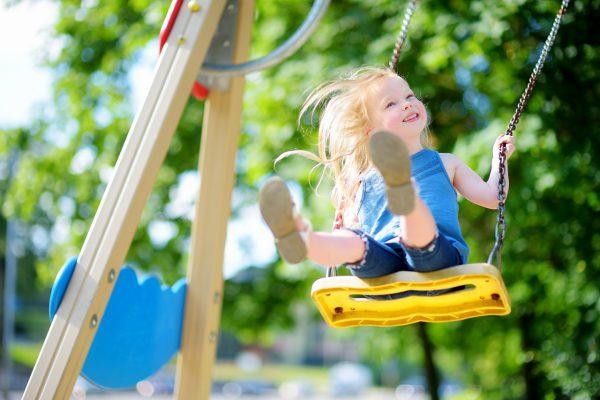 晴天の中でブランコで遊ぶ子供